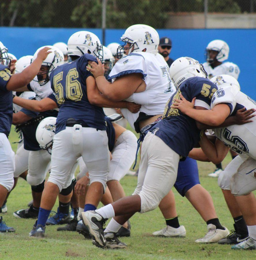Junior Dean Khazanov tackles fellow teammates  during a practice drill. He has been playing football since his freshman year.