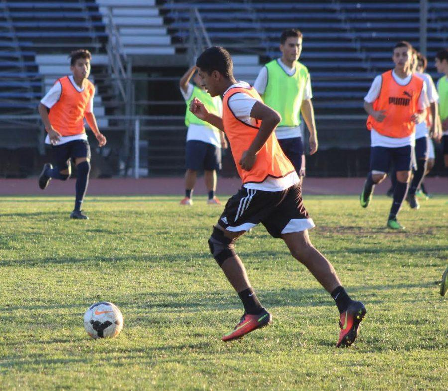 Junior Kevin Garcia dribble kicks across  the field during soccer practice at Birmingham Charter High School.