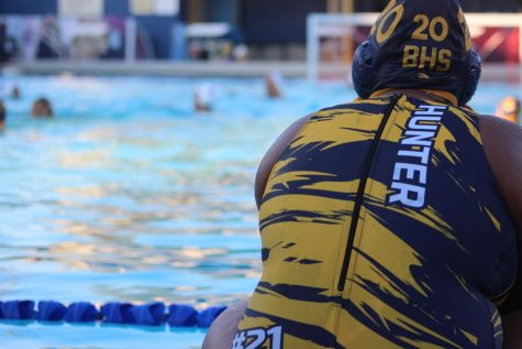 Varsity water polo player watches her team