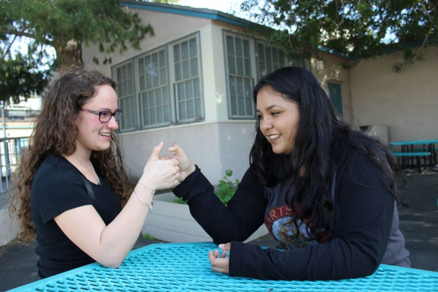Valedictorian+Rebekah+Spector+and+salutatorian+Elsie+Morales+have+a+thumb+war+during+their+free+time.