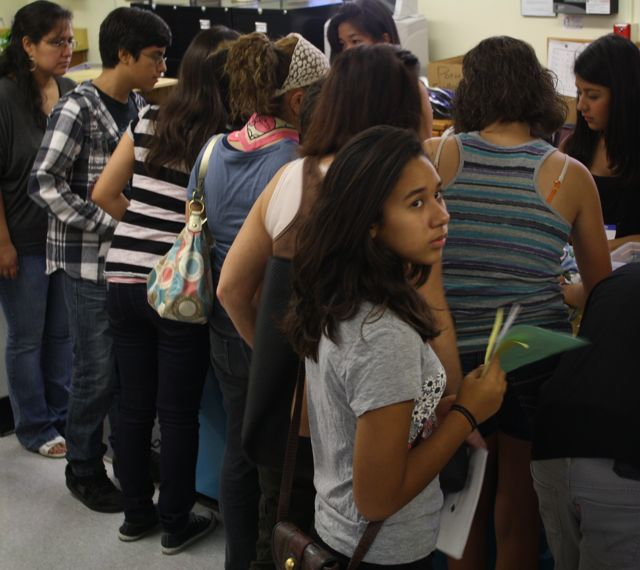 Photo by Brayan Cecenas. New and returning students at Daniel Pearl Magnet High School gather in the main office during orientation on August 8 to receive their schedules and locker assignments.