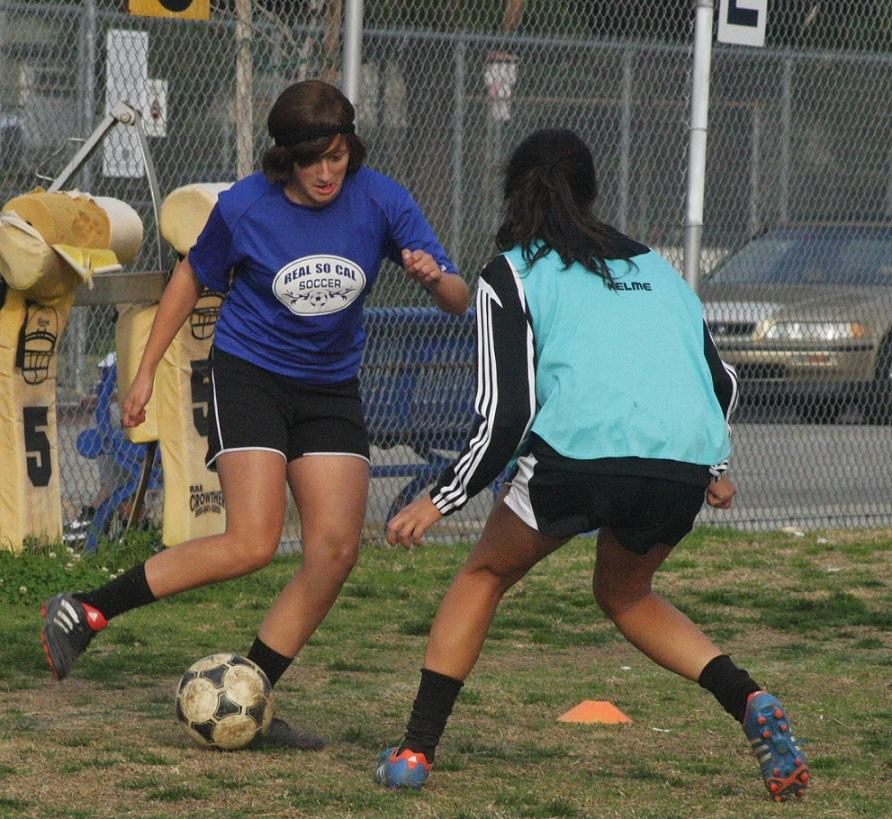 Photo by Robert Tapia. Varsity Girls' striker Hailey Pohevitz maintains the ball during a practice game.