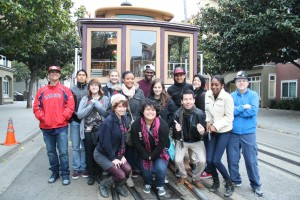 Fifteen journalists are in front of a trolley cart in San Francisco on their way to dinner and the Ghirardelli Square.