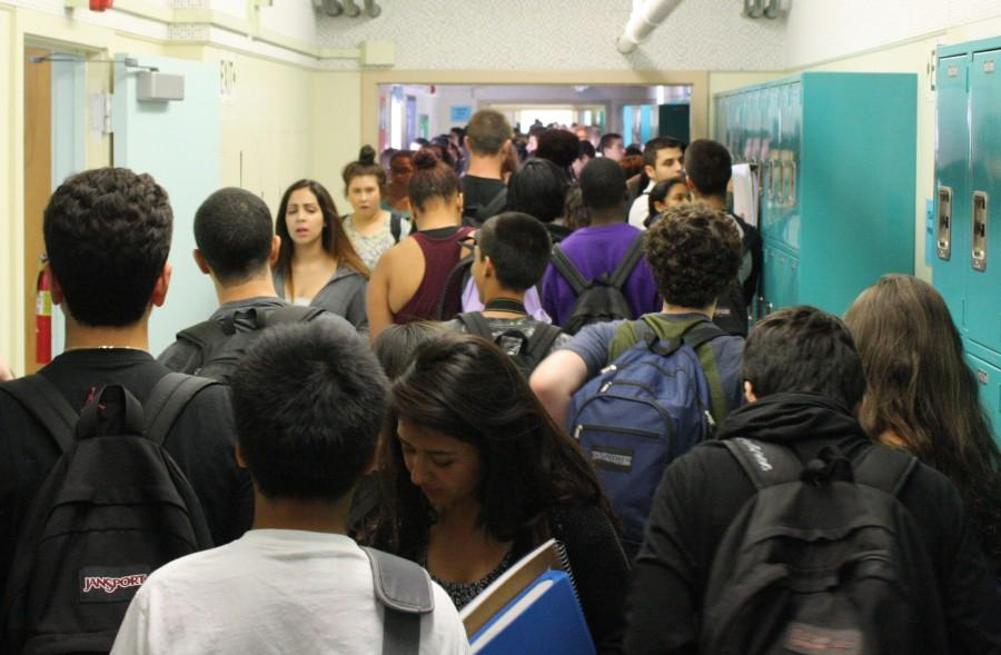 """Students crowd the hallways during passing period before their next class. Some take advantage of the """"no locker"""" rule  while others still use their lockers to get their books, mingle with friends or simply waste time. Photo by Jake Dobbs"""