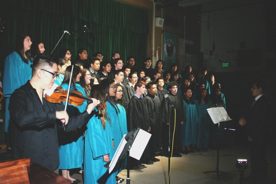 """Daniel Pearl Magnet High School's choir sings three musical pieces beginning with """"Shalom Alecheim"""" with Daniel Lee (left) on the violin and Gor Mkrtchian (right) conducting. The next two pieces include """"Shir l'Shalom"""" and """"Next to Me,"""" which featured soloists.  Photo by Jake Dobbs."""