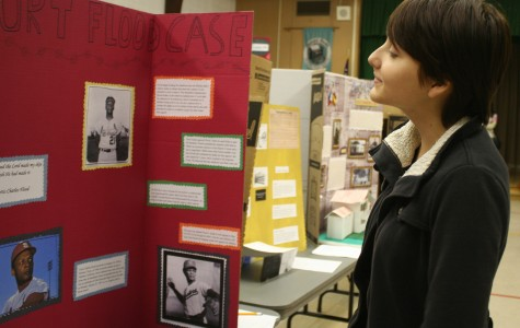 Senior Kendall Tucker reads through a tri-fold that talks about  Curt Flood's major change in baseball history. Photo by Alex Torres.