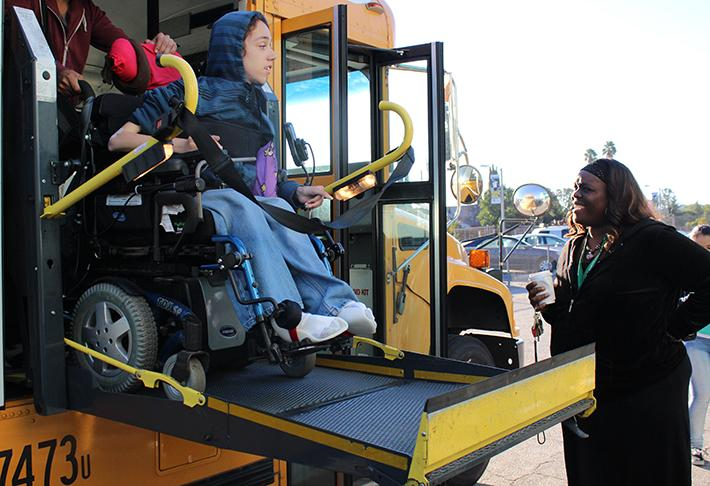 School security Madgeolyn Wooten waits for freshman Justin Taylor to get off the bus during her morning routine.