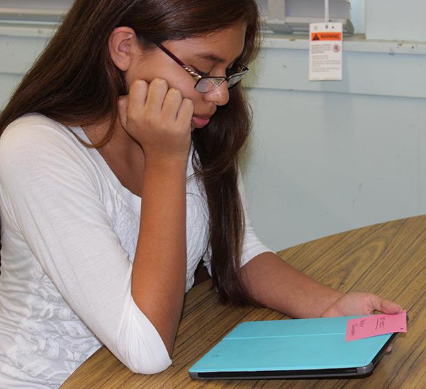 "Freshman Angel Rivera looks at her ""No Nook"" Post- It on her device to replicate what she did during her Life Unplugged project to stay away from electronics for 24 hours."