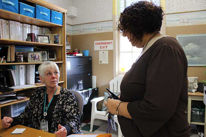 School Administrative Assistant Diane Seiger communicates with officer administrator Lupe  Osorio about the day's plans.
