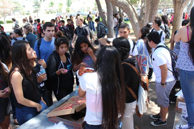 Seniors distribute slices of pizza as part of their dance ticket during Fiesta Friday. Due to district restrictions, the senior class will have to give 50 percent to the general study body.