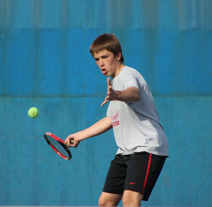 Sophomore Jozsef Feher positions his racket to return the tennis ball during practice on Birmingham's tennis courts.