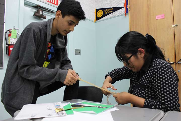 Junior David Diaz and senior Vanessa Fano cut duct tape to make braids and use them as arm tassels for Diaz's outfit. In order to compensate for not having as much time to work together on weekends, they work in classrooms during nutrition and lunch.