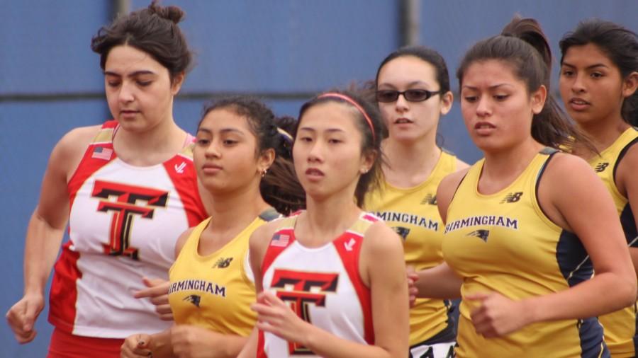 Birmingham runners Sherran, Savannah Orrill, Natalie and Kayla run alongside their competitors Taft runners during a track meet on April 22.