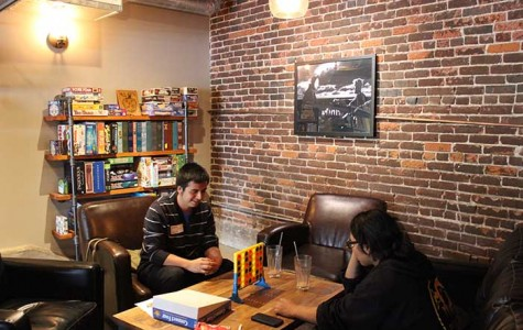 Two costumers play Connect 4 while drinking refreshments from the store's Cafe.