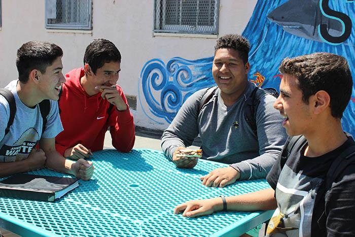Freshmen Joseph Martinez, Andy Lopez, Joey Williams and Rogae Assad talk at a table that sits in the sun during lunch.