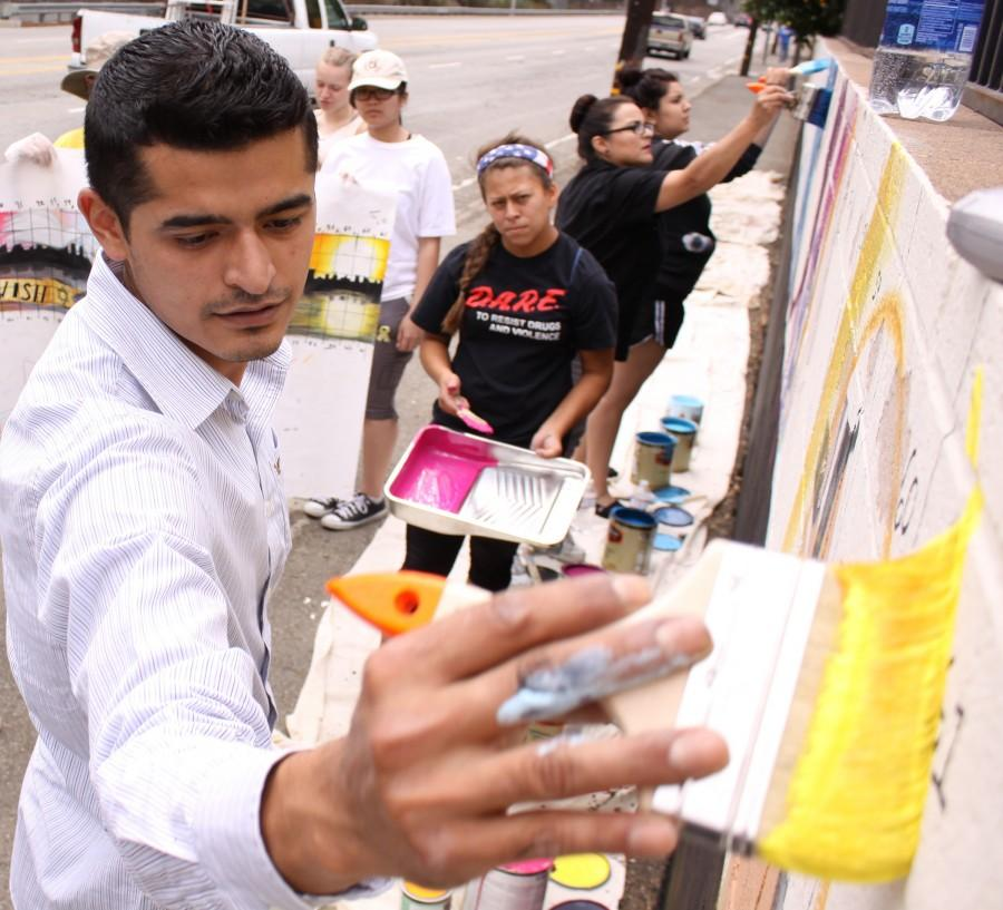 Muralist Levi Ponce demos how to apply base layers of color onto the wall to volunteers on May 23. Ponce patrolled the mural site, offering help to any volunteer he saw struggling.