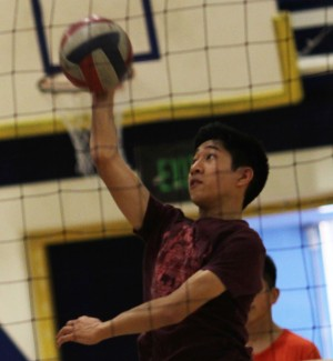 Sophomore Jonas Acebes jumps high in the air trying to spike the volleyball over the net.