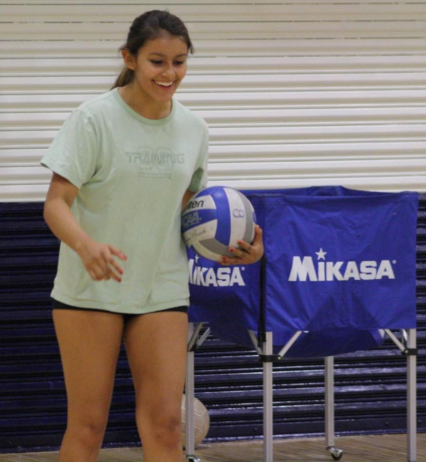 Senior Siena Tinoco smiles as she prepares to serve the ball across the volleyball court to her teammates on the other end.