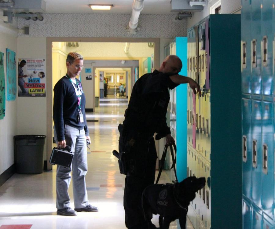 Principal Deb Smith watches as Officer Matthew Felts demonstrates a locker search with his canine partner Meeko.