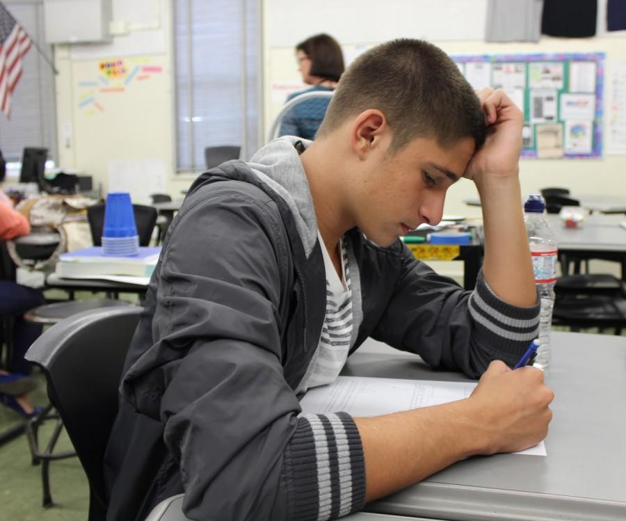 Senior Maxim Grinfeld works on a handout during a monthly math competition.