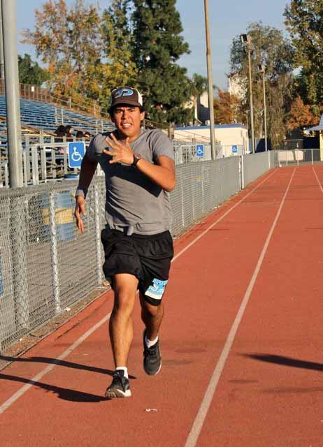 Senior Pedro Morataya shows his Shark pride while running down the track.