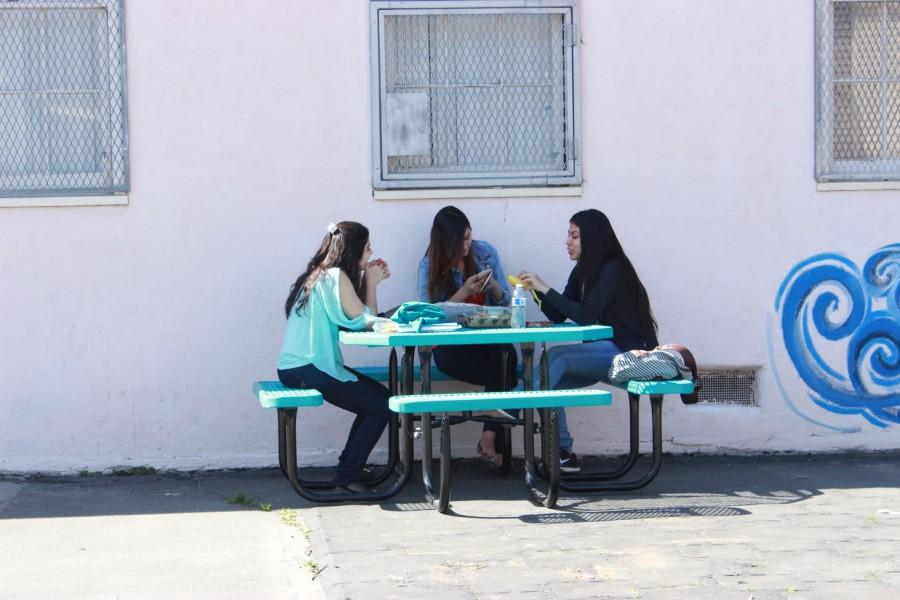 Students move the lunch table next to a wall to shade themselves from the sun.