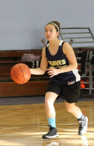 Junior Erica Mallari dribbles down the court eyes on the basket ready to make a shot.