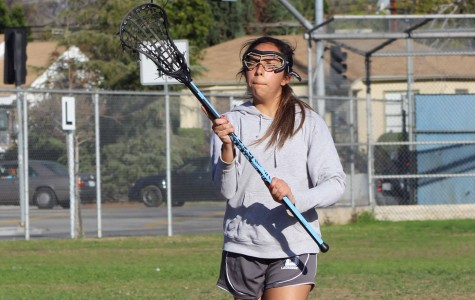 Junior April Serrano holds her stick up ready to catch the ball on the run at Birmingham Community Charter High School. The CIF championship is back on for the Lady Patriots.