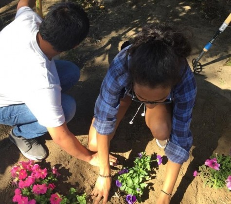 Alumni Ludyn Vasquez and Imani Brown plant flowers during last year's Sparkle Saturday event.