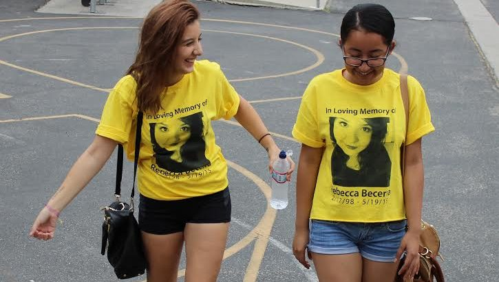 Seniors Valentina  Comar and Sindy Saravia  walk beside each other clad in their Rebecca Becerra shirts in remembrance of her. Bacerra committed suicide last year  in May.  Students were deeply impacted by her death and adorn themselves in yellow ribbons to fight teen suicide.