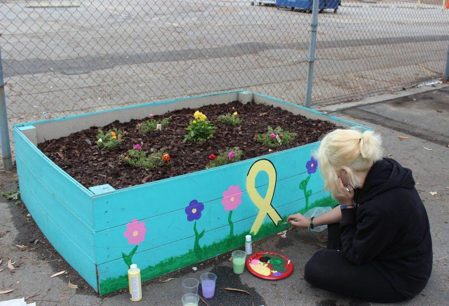 Senior Jo Cortes paints a garden with a yellow ribbon on the newly planted suicide awareness garden.