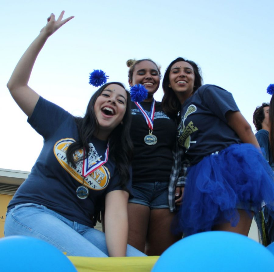 Seniors Andrea Escimilla, Tahra Hunter and April Serrano cheer on top of their float in excitement for the game ahead.