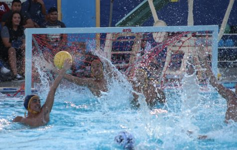 Boys water polo team reaches for the ball