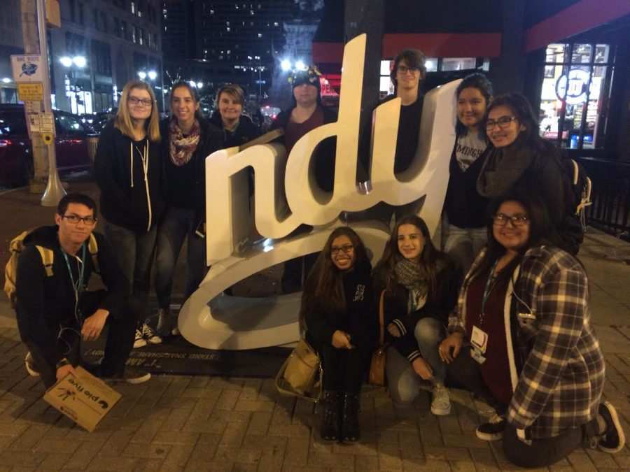 Students pose next to an Indy statue on Saturday night.