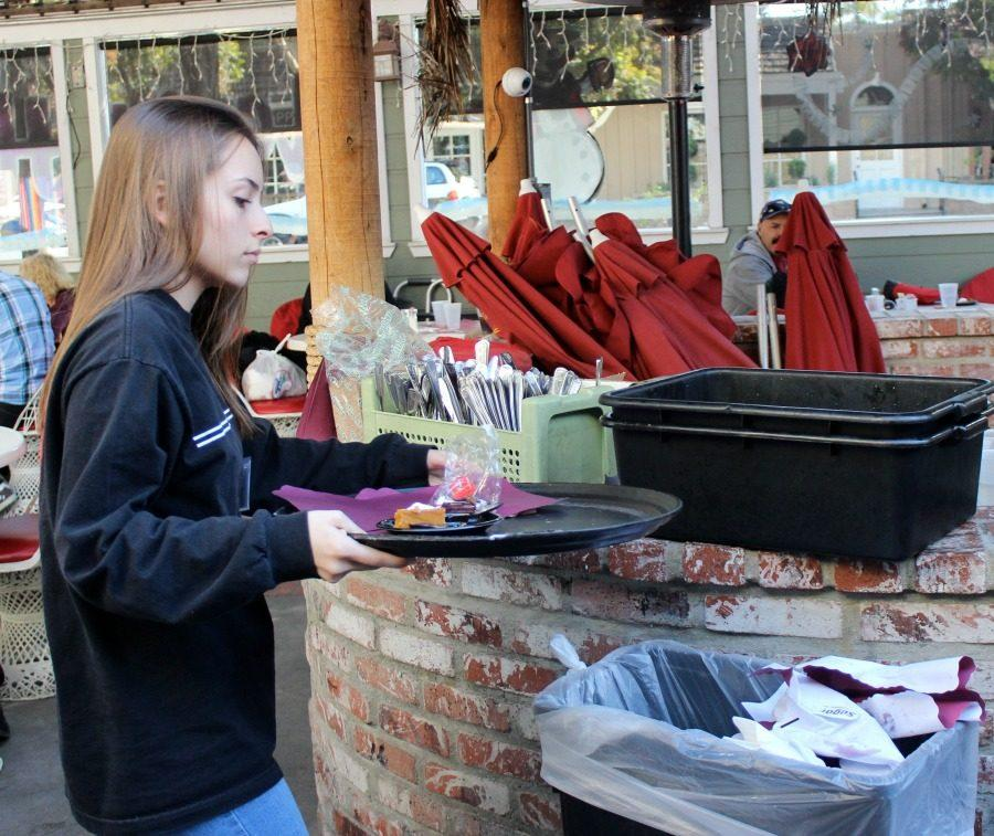 Junior Ani Kocharyan empties a food tray while volunteering on Thanksgiving. She volunteered on an event that helped provide senior citizens with a holiday meal.