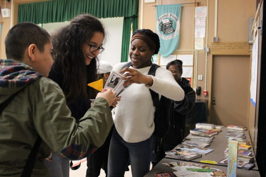 Juniors Lisset Bayardo, Francheska Vicents and Jade Ajileye share a brochure at the Black History Month event held in the Multi Purpose Room on Friday.