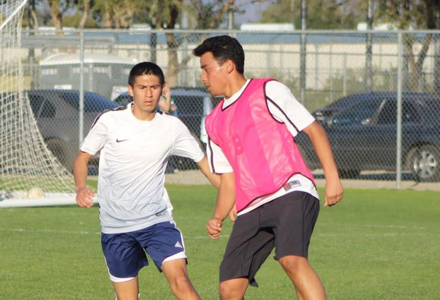 Varsity player Adonis Arevalo dribbles the ball to keep it away from his opponent during practice.