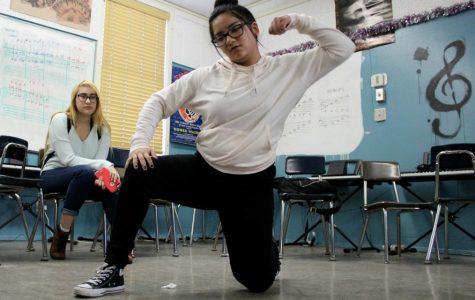 Junior Harmony Sanchez practices her hip-hop choreography as junior Sandra Ortega watches.
