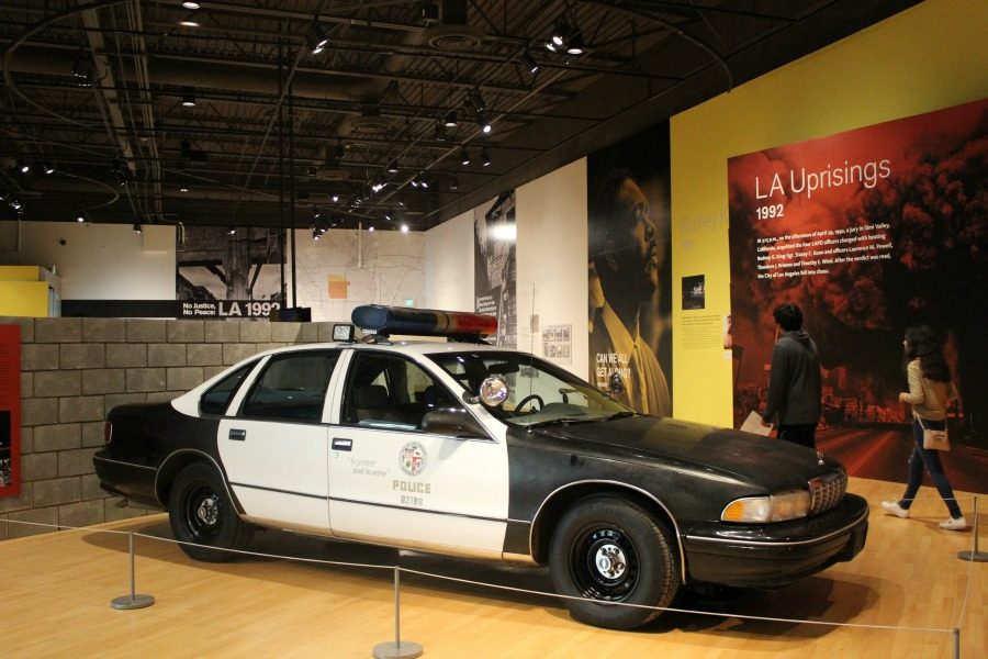 The California African American Museum used the display of an LAPD car in front of a brick wall to demonstrate what the environment was like during the  me of the riots.