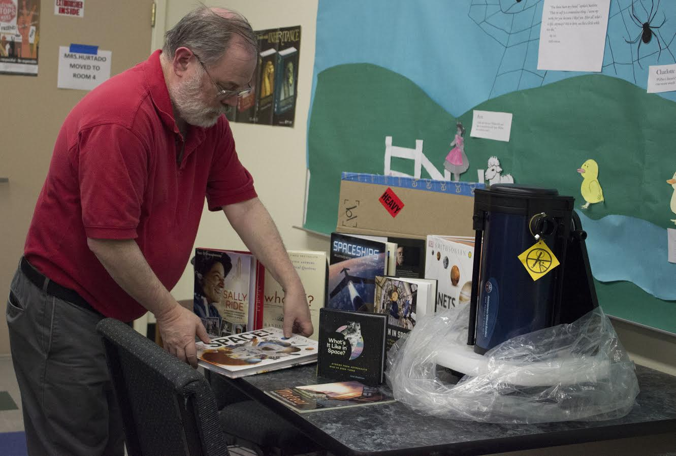 Science teacher Mr. Schaffter sorts through the Rotary Clubs donation of astronomy books and telescopes.