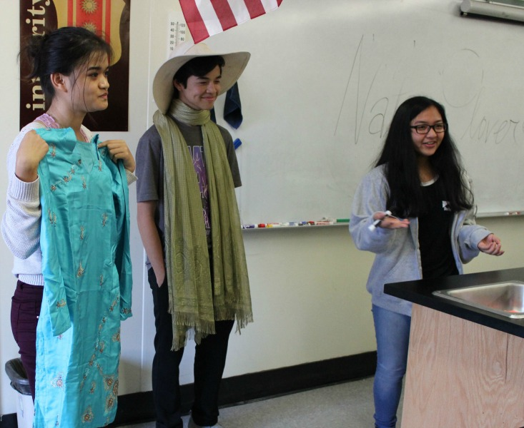 Sophomore Karina Mara explains the clothing choice of sophomores Christine Valenzuela and David Mallari during the Fashion Show.
