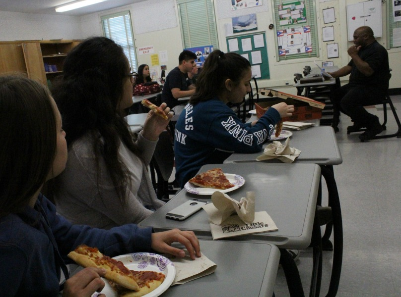 Juniors Ani Kocharyan, Francheska Vicents and Ruzanna Manvelyan munch on pizza while listening to pastor Gary Smith speak about scripture.