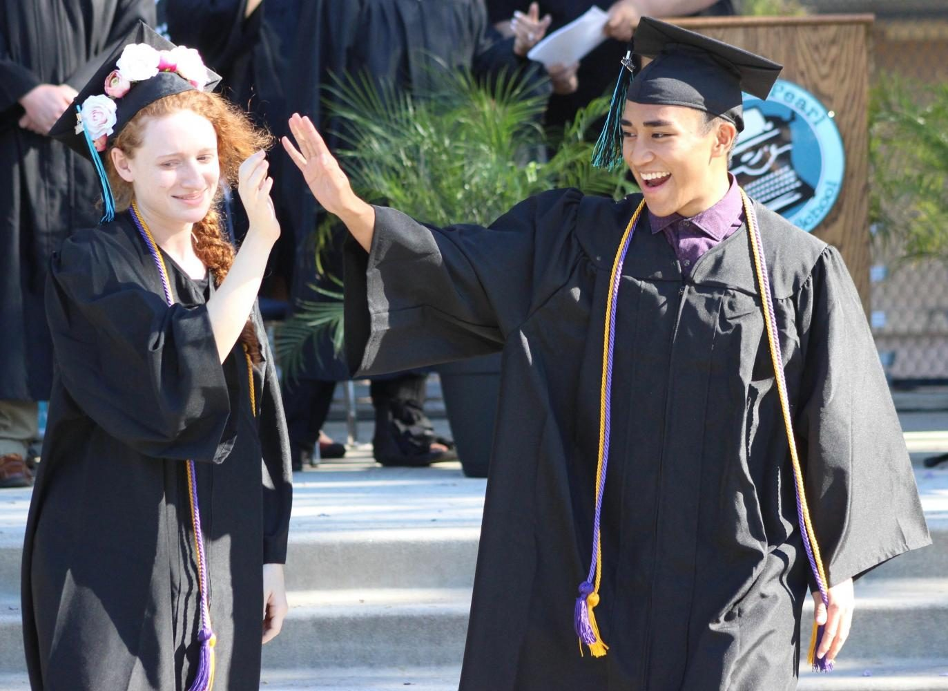 Raquel Dubin and Chester Castro congratulate each other after walking across the stage during the commencement ceremony.