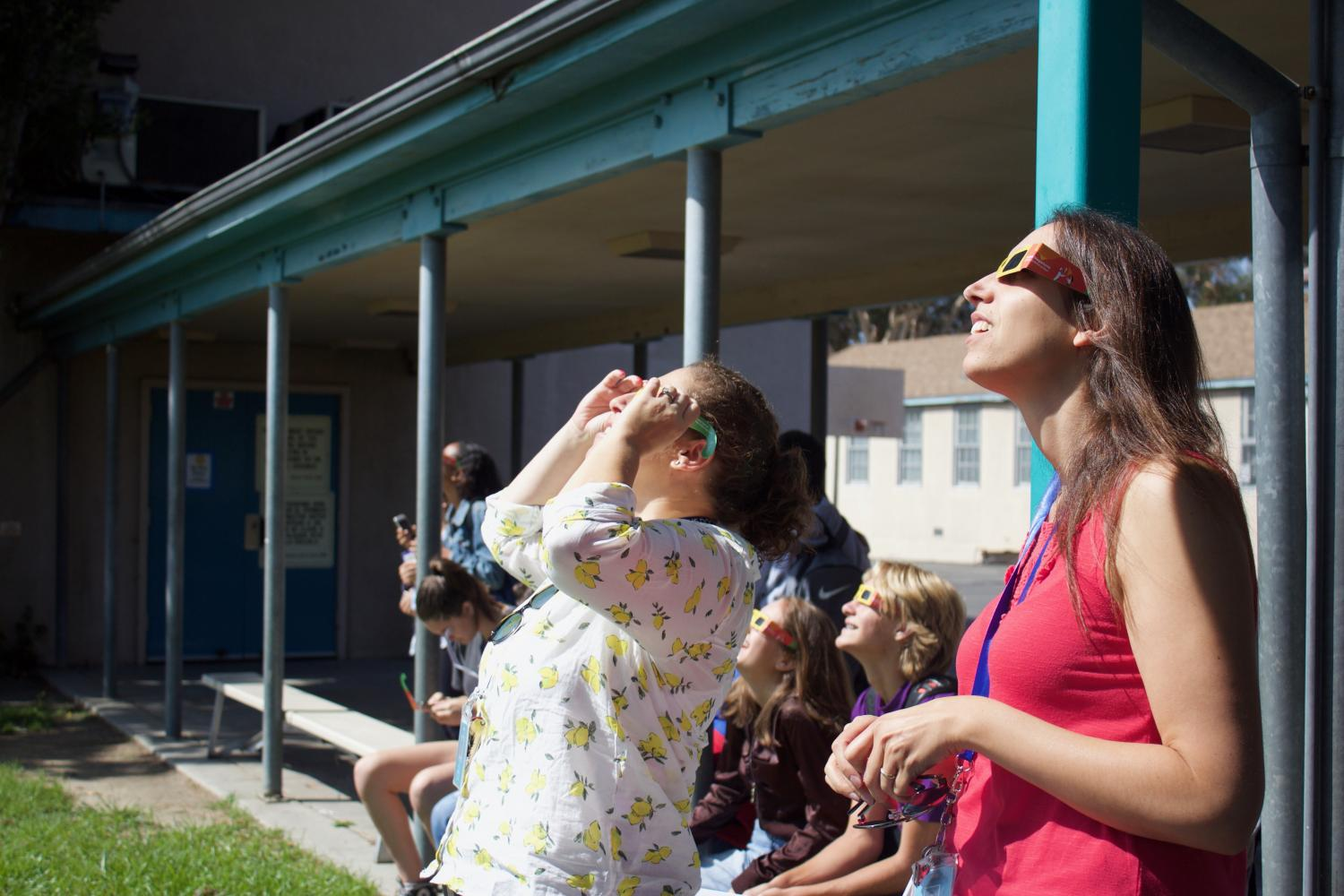 English teachers Leah Pevar and Cinthia Wald-Barry view the eclipse during nutrition today.