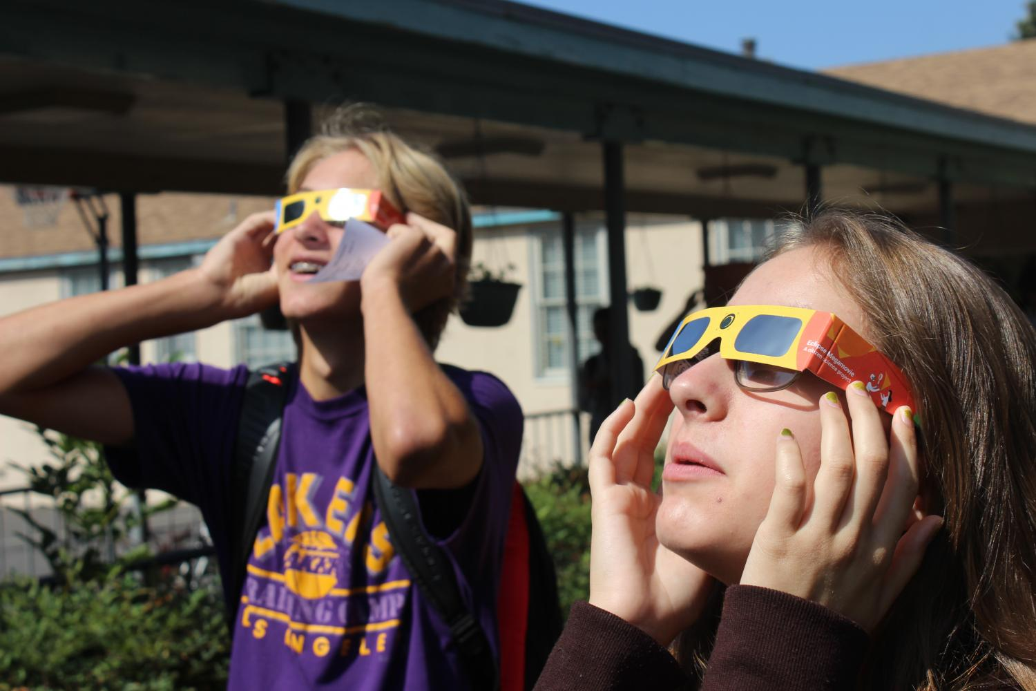 Sophomore Cuyler Huffman and junior Lauryn Ulenberg admire the view of the solar eclipse.