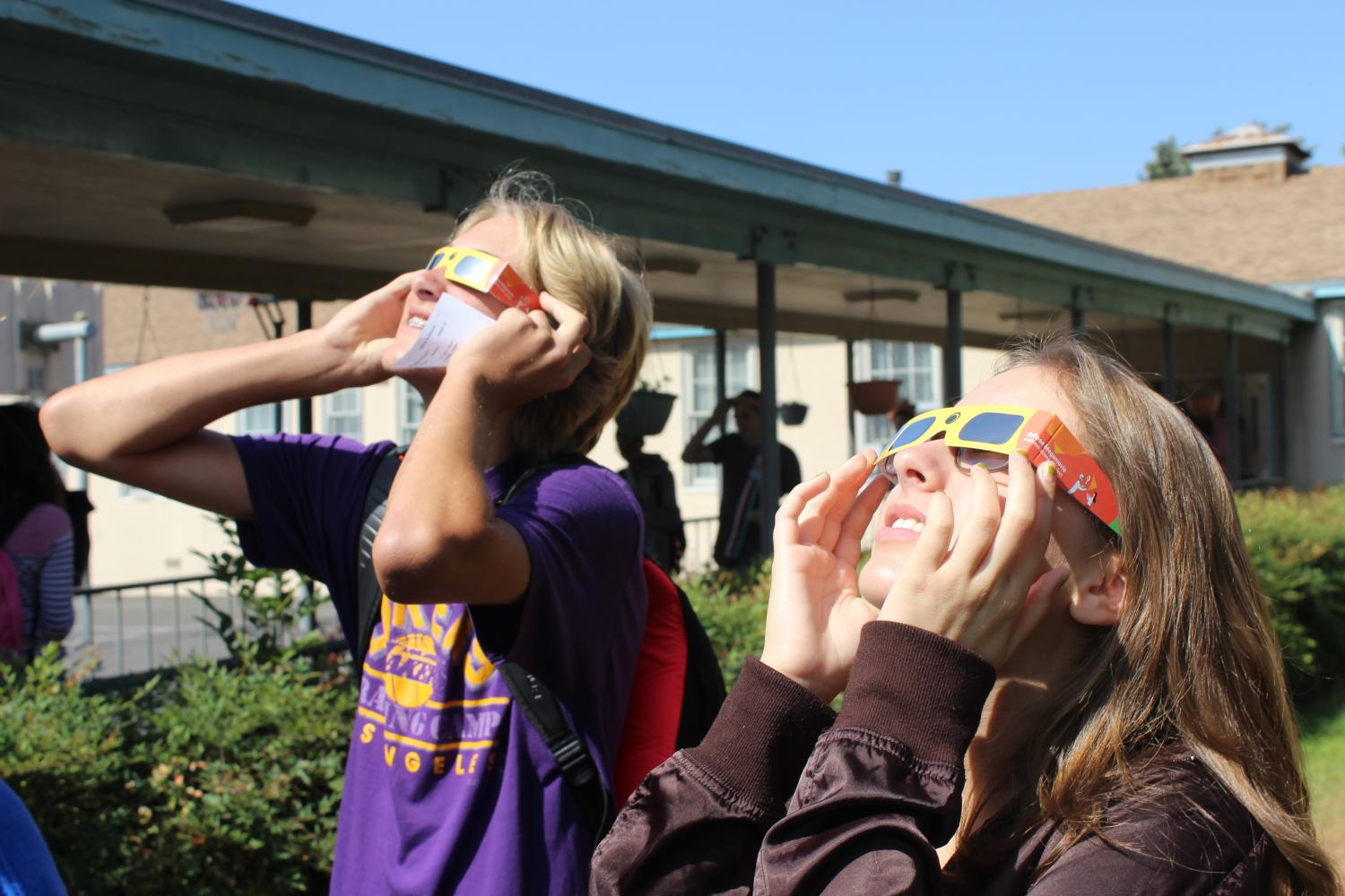 Sophomore Cuyler Huffman and junior Lauryn Uhlenberg view the eclipse using special glasses.