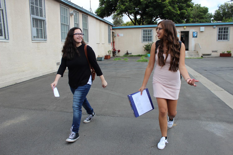 Freshman Trinnity Bayardo walks to her next class with senior Angel Rivera's guidance.