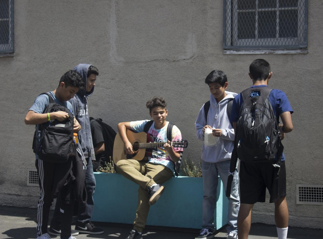 Daniel Lopez plays the guitar while his friends group around him to hear his groovy music.