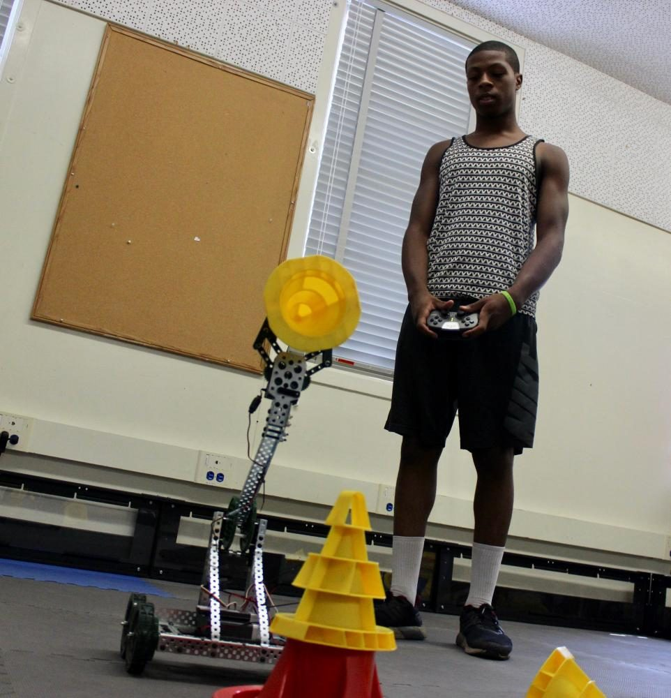 Senior Tatanka Baskerville test out a robot he constructed with his group