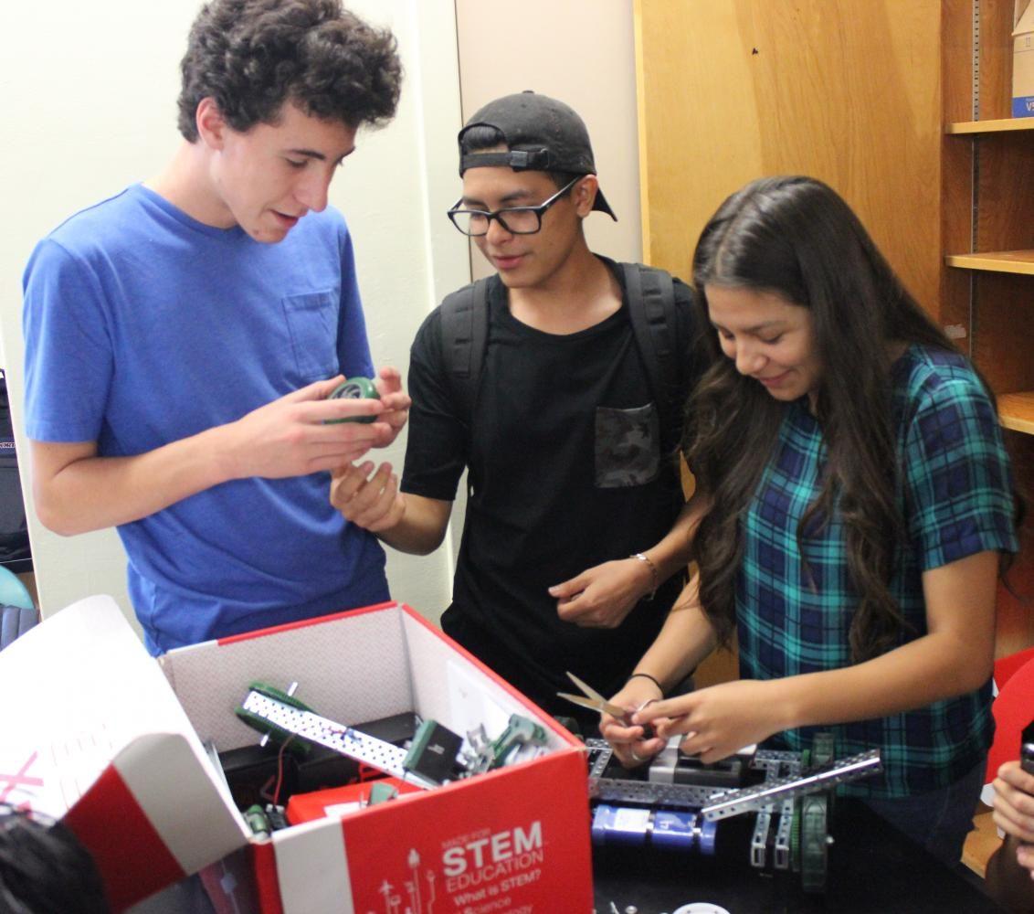 Sophomore Ethan Guttman, senior Cris Martinez and senior Deborah Zuleta  assemble materials to create their robots